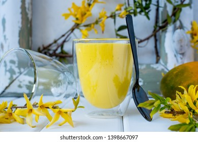 Mango cocktail, mango lassi served in a glass. Light background.