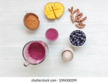Mango coconut blueberry turmeric smoothie in dlass bowl with ingredients, coconut milk in glass bottle, coconut sugar in half coconut shells, berries,  turmeric root on light blue table