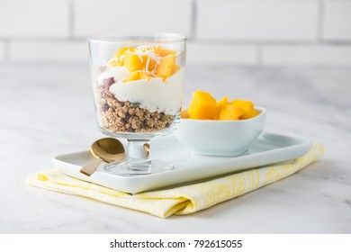 Mango coconut granola yoghurt dessert breakfast in a white setting