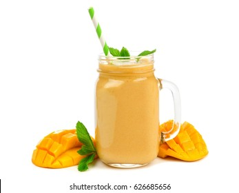 Mango coconut smoothie in a mason jar glass with mint and straw isolated on white