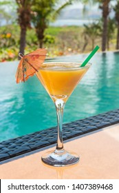 Mango daiquiri on a glass table by the pool in the summer