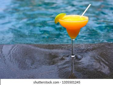 Mango daiquiri on the pool background, selective focus. Tropical holidays