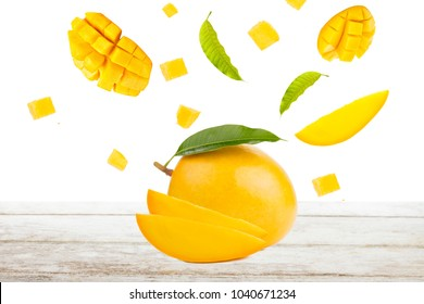 Mango and falling of cut slice with leaf on white wood, isolated background