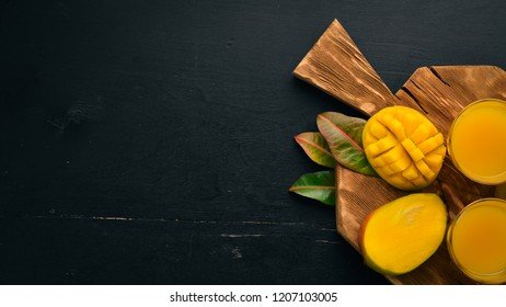 Mango and fresh juice on a black wooden background. Tropical Fruits. Top view. free space for your text.
