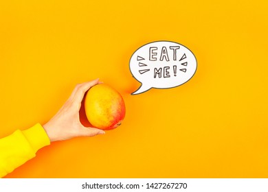 Mango fruit in creative conceptual top view flat lay composition with lightbox bubble with Eat me handwritten slogan isolated on bold color background in minimal style with copy space. Pop art poster