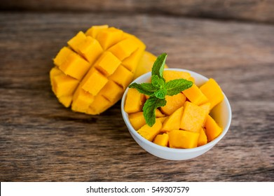 Mango fruit and mango cubes on the wooden table. Tropical fruit concept.