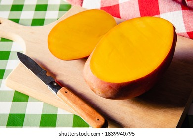 Mango fruit cut in half, next to the knife