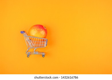 Mango fruit in shopping cart in creative conceptual top view flat lay composition isolated on bold orange color background in minimal style with copy space. Pop art poster
