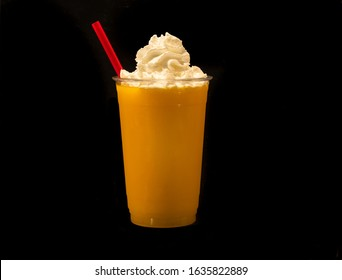 Mango Fruit Smoothie in a clear plastic cup with whipped cream and a straw against a black background.