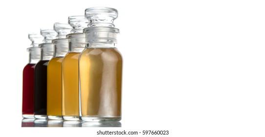 Mango, grape, apple, and white vinegar in glass vial over white background