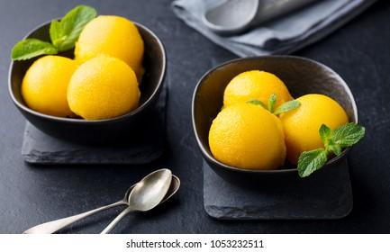 Mango ice cream, tropical fruit sorbet in black bowl on slate background.