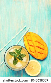 mango ice tea with mint in a glass  on  blue  wooden background . top view. toning