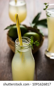 Mango juice OR Aam Panna or Panha in a transparent glass with whole green fruit, selective focus
