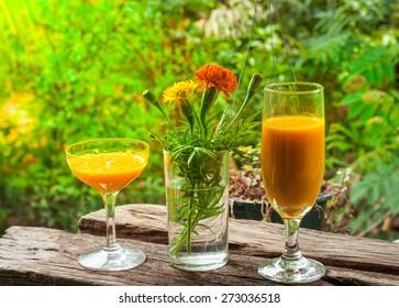 Mango juice in glass on wooden plank