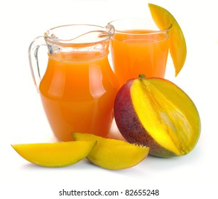 mango juice in a jug and a glass of fruit