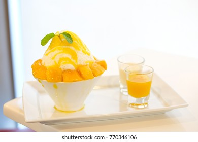 Mango kakigori (Japanese shaved ice dessert flavor with mango ice-cream) or bingsu (Korea dessert) serve on white bowl with yellow mango sauce & white milk for sweet food background or texture.