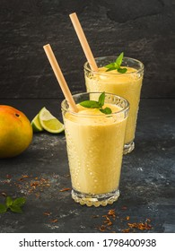 Mango lassi dessert in decorative glasses with fresh mint and lime. On a black background in natural light. Ecological drinking tubes.