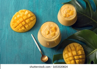 Mango lassi drink in glasses and mangoes on tropical leaves