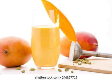 Mango lassi in a glass decorated with a cut mango fruit chip. Two entire mangos and cardamon seeds, some crushed on a wooden cutting board. A metallic pestle. Close up. White background.