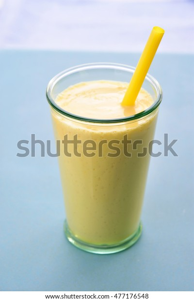 Mango lassi in glass with straw. Mango smoothie made with mango and yogurt, yoghurt. Selective focus. Angle view.