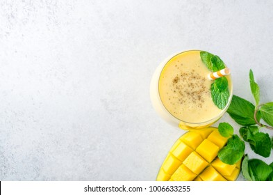 Mango lassi with mint leaves, traditional indian drink in glasses on a light gray stone table. Top view, horizontal image, copy space