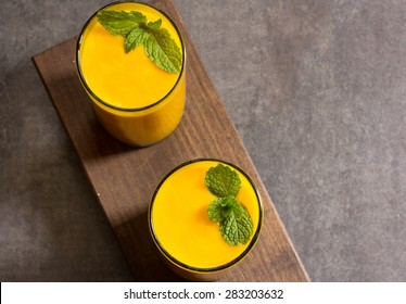 Mango lassi with mint on top, overhead view with copy space