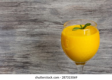 Mango Lassi on wooden background, selective focus