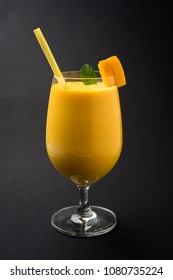 Mango Lassi or smoothie in big glass with mint leaf. Side angle  Isolated over colourful background. Selective focus