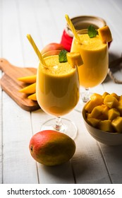 Mango Lassi or smoothie in big glasses with curd, cut fruit pieces and blender