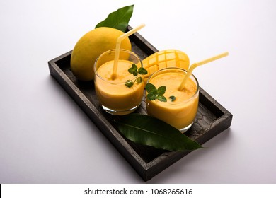 Mango Lassi or yogurt, Indian popular summer drink served in glass with whole Alphonso Aam fruit, selective focus