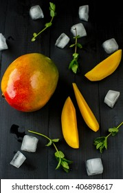 Mango on a black wooden background with mint and ice cubes