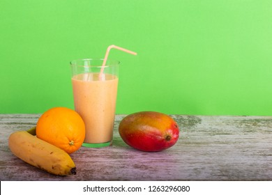 Mango, Orange and banana smoothie in wood table with green background