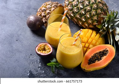 Mango and papaya smoothie with tropical fruits, pineapple and passion fruit, exotic vitamin drink