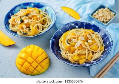 Mango pepper peanut pasta on a stone background. toning. selective focus