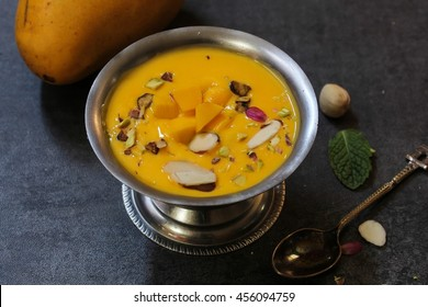 Mango Phirni - Indian Mango milk pudding topped with nuts, selective focus