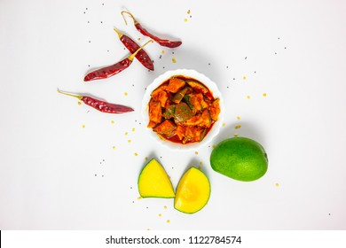 Mango pickle top view with chillies and raw mango isolated on white background