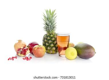 Mango, pineapple, lemons, apples, pomegranates and fruity juice on white background close-up.