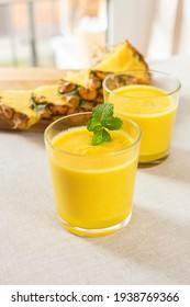 Mango with pineapple smoothie in jug and glasses. Fresh morning breakfast on the table for slimming with yellow fruit