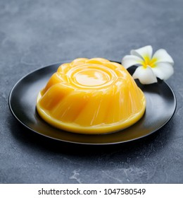 Mango pudding, jelly, dessert on black plate. Grey stone background.