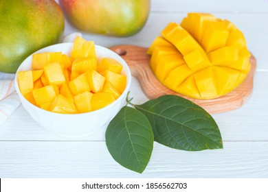 mango slices in a bowl and on a cutting Board close-up. white background with mango.