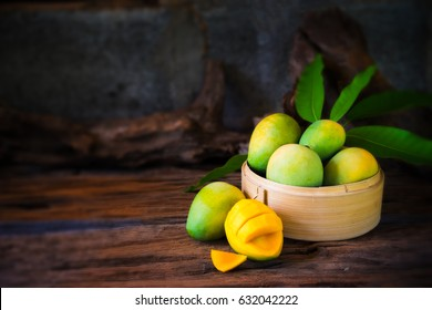 mango and mango slices on a wooden table