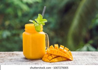 Mango smoothie in a glass Mason jar and mango on a green background. Mango shake. Tropical fruit concept.