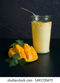 mango smoothie / mango lassi in vintage glass cup on a dark surface with metal straw. with mint leaves and a slice of ripe and juicy mango