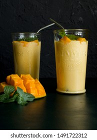 mango smoothie / mango lassi in vintage glass cups on a dark surface with metal straws. with mint leaves and a slice of ripe and juicy mango