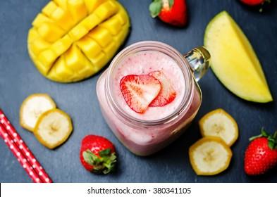 Mango strawberry banana smoothie on a black background. toning. selective Focus