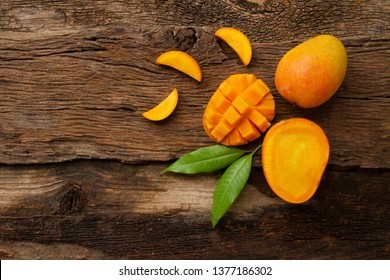 Mango tropical fruit with green leaf on dark brown wooden table background, top view