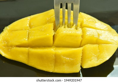 mango tropical fruit slice dice shape stabbing by silver fork on plate