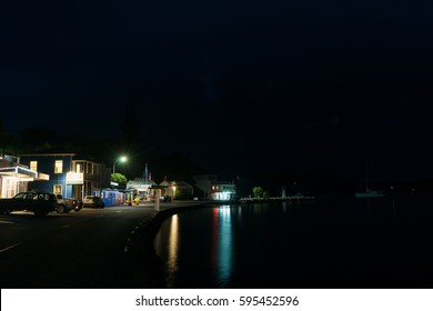 MANGONUI, NEW ZEALAND - FEBRUARY 13; Small New Zealand coastal town main street at night lights from buildings and street glow in calm water on February 13, 2017  Mangonui New Zealand