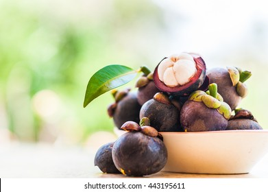 Mangosteen and cross section showing the thick purple skin and white flesh of the queen of friuts, Delicious mangosteen fruit arranged on a bowl, Mangosteen flesh, closeup. Mangosteen.