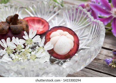 mangosteen fruits in glass bowl with garden flowers